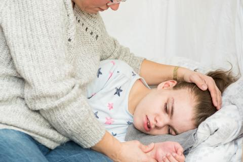 Child lying in bed being cared for