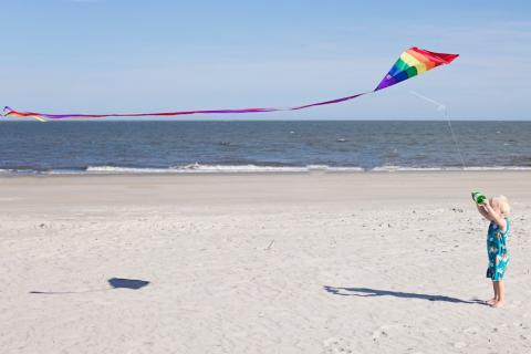Child flying a kite on a beach