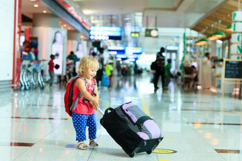 A child pulling a suitcase in an airport