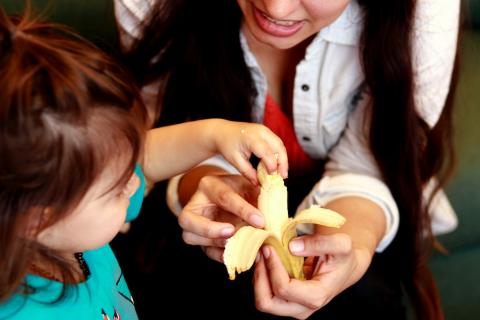 Mother giving child a banana