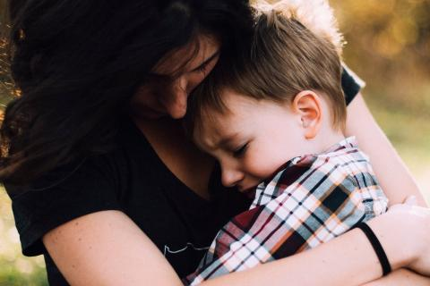 Mother hugs crying son