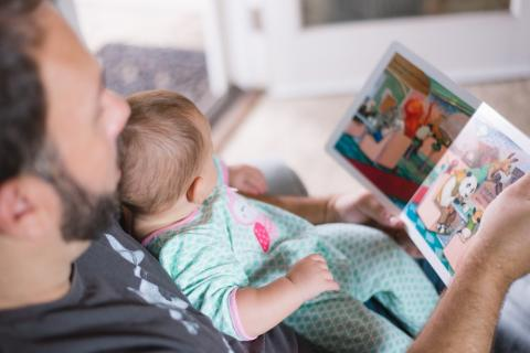 Dad reading to baby for World Book Day