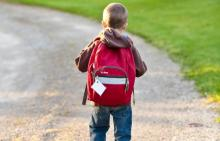 Boy walking to school with backpack