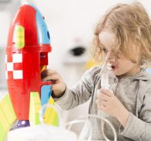 A child with cystic fibrosis uses a nebuliser while playing