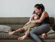 Mum and child hug on sofa