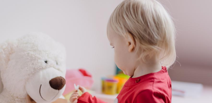 Child giving a teddy a present