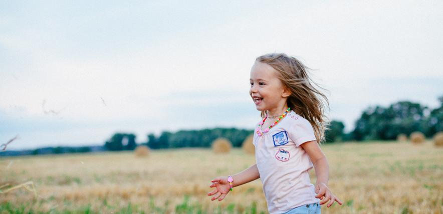 Happy little girl running in a field