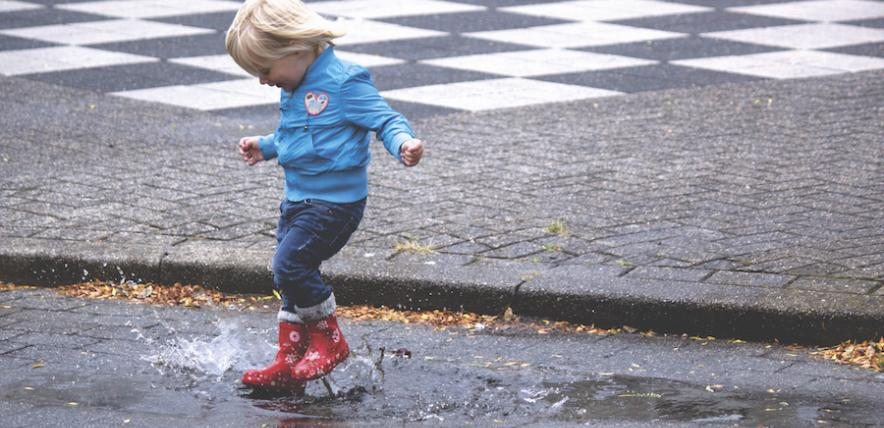 Boy splashing in puddles